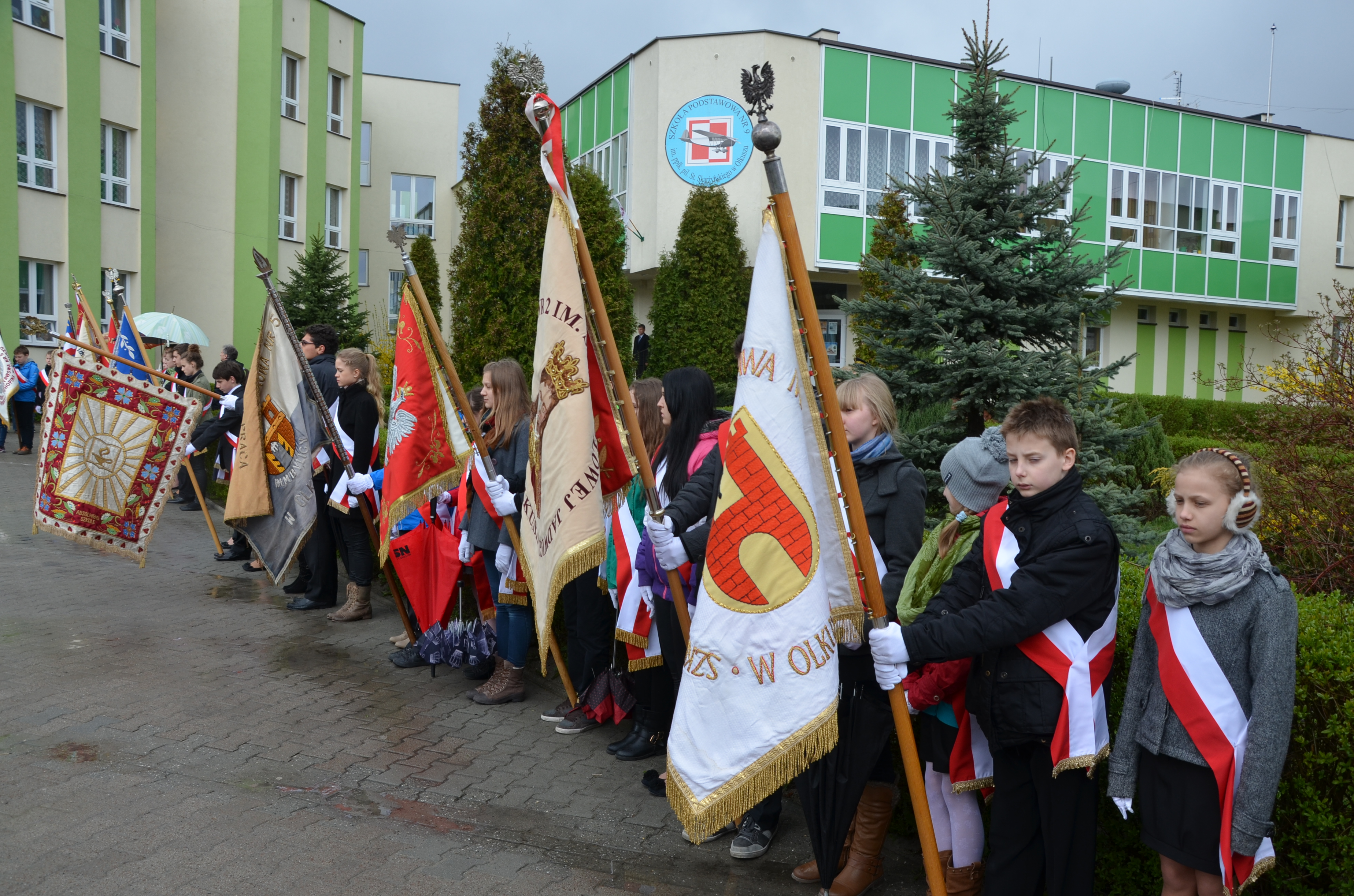 Grupa uczniów ze sztandarami szkolnymi stoi przed pomnikiem