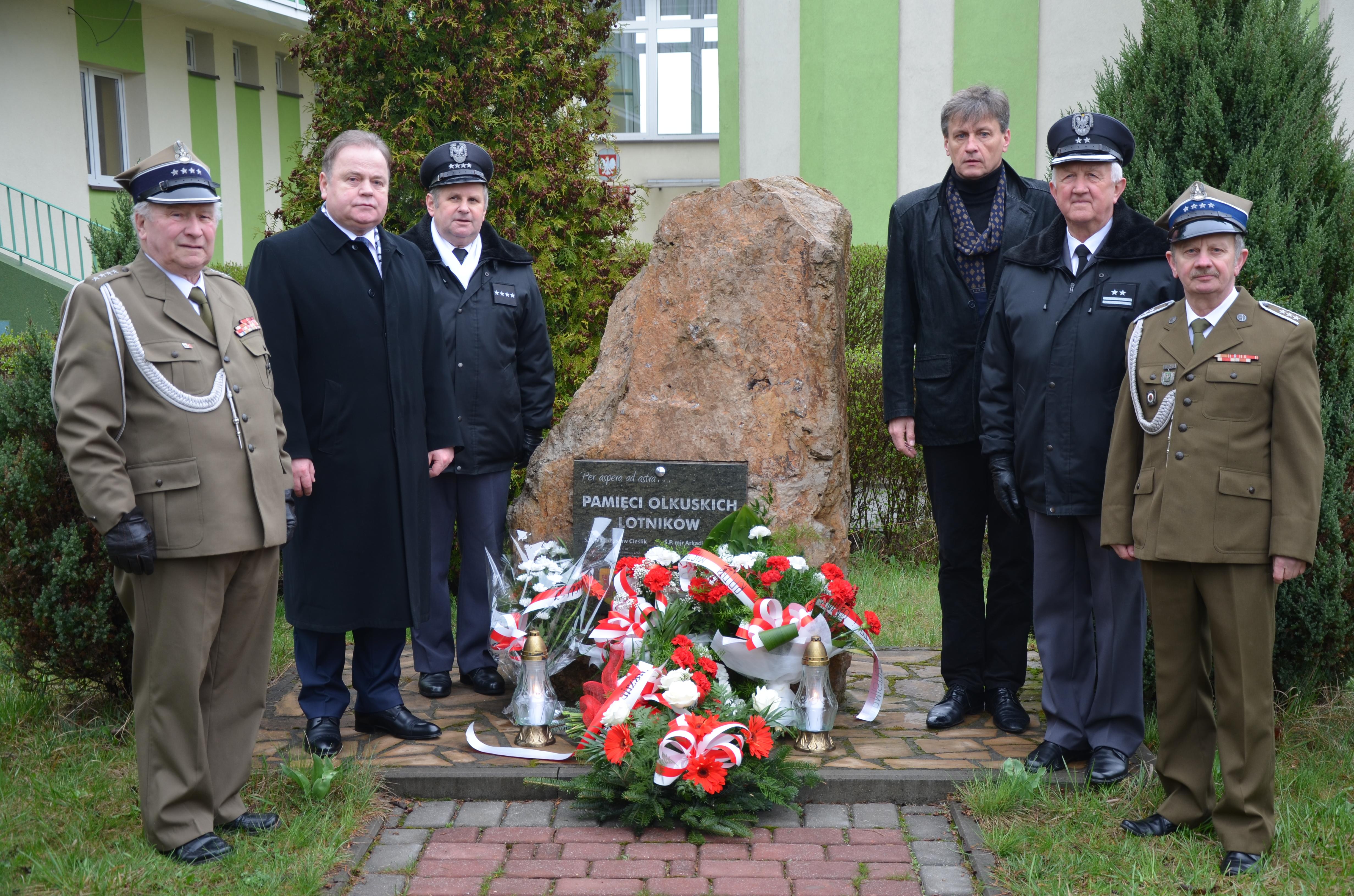 Grupa sześciu mężczyzn stoi obok pomnika