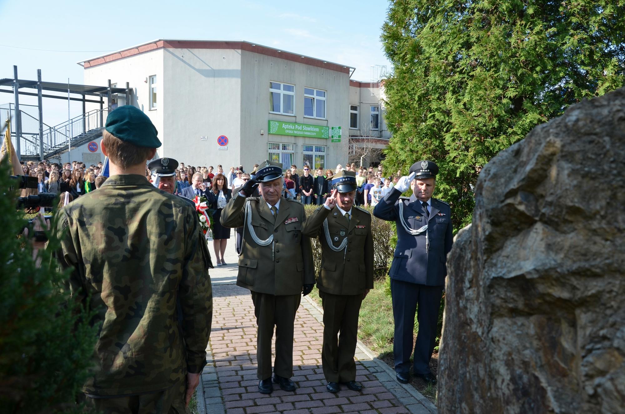 Mężczyźni w mundurach wojskowych salutują przed pomnikiem